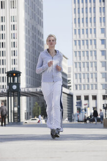 Germany, Berlin, Young woman jogging in city - SKF00060