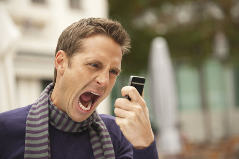 Germany, Bavaria, Munich, Man holding mobile phone, screaming, portrait - WESTF14054