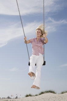 Germany, Schleswig Holstein, Amrum, Woman on swing - RBF00172