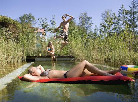 Austria, Salzburger Land, Teenagers (14-15) at garden pool, having fun - WWF01124
