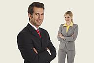 Businessmen smiling, women in behind, arms crossed. - WESTF14590