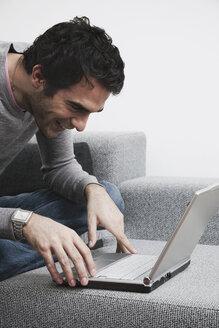 Man sitting on sofa using laptop, smiling - WESTF14371