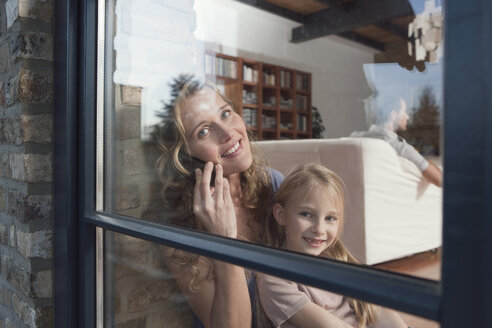 Germany, Cologne, Mother and daughter (6-7) sitting by window, mother using mobile phone, portrait - WESTF14353