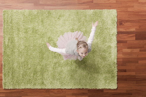 Germany, Cologne, Girl (6-7) playing on carpet, looking up, elevated view - WESTF14314