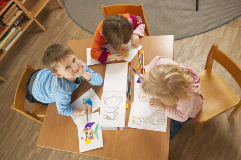 Germany, Children in nursery sitting at table drawing pictures, elevated view - RNF00222