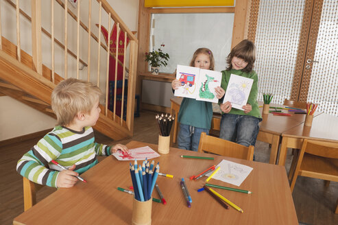 Germany, Children in nursery, girls (4-5), (6-7) in background holding paintings, smiling, portrait - RNF00159