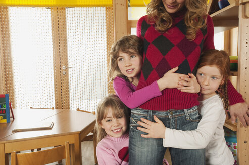 Germany, Nursery, Female nursery teacher and children playing together - RNF00120