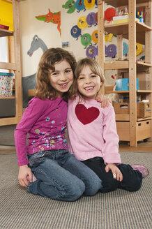Germany, Two girls (4-5), (6-7) in nursery sitting on floor, embracing, portrait - RNF00087