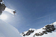 Austria, Arlberg, Man skiing downhill, doing jump, low angle view - MIRF00031