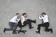 Three business people, business man pushing businesswoman in office chair, side view, elevated view - BAEF00079