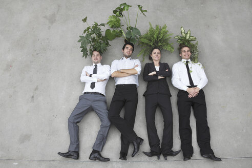Business people standing side by side, foliage plants on their heads, elevated view - BAEF00067
