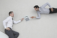 Two businessmen using calculator, side view, elevated view, portrait - BAEF00055