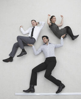 Businessman lifting two colleagues, smiling, portrait, elevated view - BAEF00049