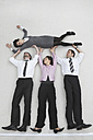 Four business people, businessmen and businesswoman lifting colleague, portrait, elevated view - BAEF00037