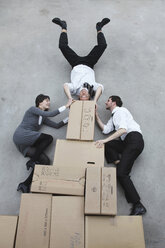 Three business people on cardboard boxes, man doing handstand, smiling, portrait, elevated view - BAEF00034