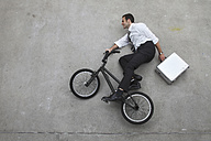 Businessman riding bicycle holding suitcase, elevated view - BAEF00031