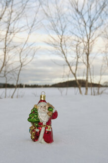 Santa claus figurine standing in snow, winter. - AWDF00488