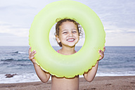 France, Corsica, Girl (2-3) looking through inner tube, smiling, portrait - SSF00056