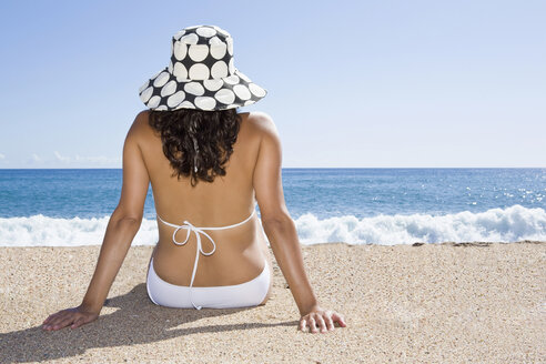 France, Corsica, Woman relaxing on beach, rear view - SSF00050