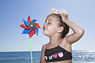 France, Corsica, Girl (2-3) blowing paper windmill on beach - SSF00047
