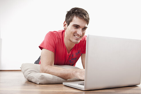 Young man lying on floor using laptop, smiling - SSF00041