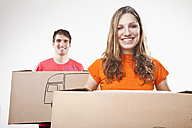 Young couple carrying cardboard boxes, smiling, portrait - SSF00038