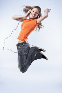 Young woman wearing headphones, jumping in air - SSF00032