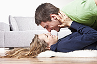 Young couple lying on floor, rubbing noses, side view - SSF00023