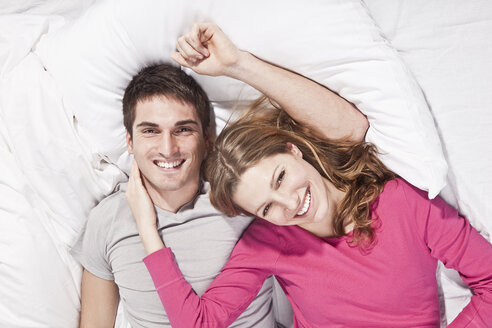 Young couple lying on bed, smiling, portrait - SSF00020