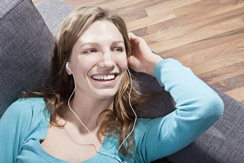 Woman relaxing on couch and listening music, smiling - SSF00014
