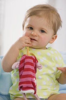 Baby girl (6-11 months) playing with toy, portrait - SMOF00425