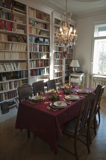 Place setting on dining table with bookshelf in background - NHF01210