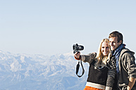 Austria, Steiermark, Dachstein, Young couple photographing on mountain, smiling - HHF03335