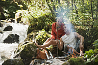Austria, Steiermark, Young couple sitting at camp fire by stream in forest - HHF03266