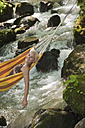 Austria, Steiermark, Woman lying in hammock above stream - HHF03263