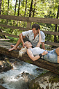 Austria, Steiermark, Couple resting on wooden bridge over stream - HHF03257