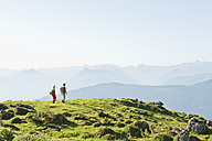 Young couple standing on mountaintop, looking at view. - HHF03236