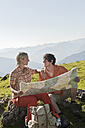 Young couple holding map, looking face to face, smiling. - HHF03230