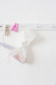 Pastries in plastic bags hanging on hook rack - COF00141