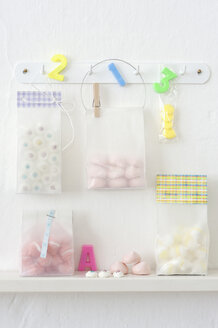 Pastries in plastic bags hanging on hook rack - COF00138