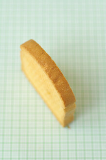 Single slice of zwieback on green background, close up - COF00108