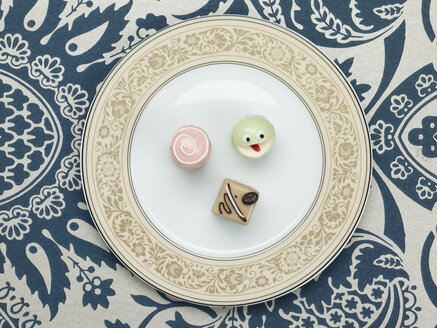 Petit fours in plate against patterned background - AKF00140