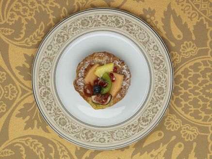 Fruitcake in plate against patterned background - AKF00134