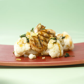 Cauliflower garnished with fried veal in plate on green background - SRSF00006