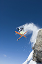 Austria, Man jumping on snow covered arlberg mountain - MIRF00054