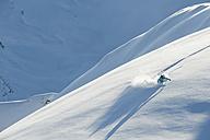 Austria, Woman skiing on snow covered arlberg mountain - MIRF00045