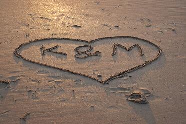 Belgium, De Panne, Text written in heart shape drawn in sand on beach - KJF00081