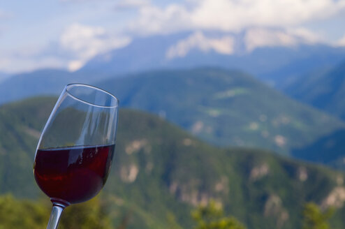 Italy, South Tyrol, Close up of wine glass with dolomite alps in background - SMF00626