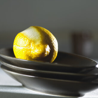 Lemon on stack of plates, close-up - SRSF00040