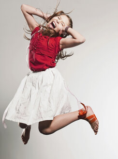 Girl (10-11) jumping and shouting - FMKF00100